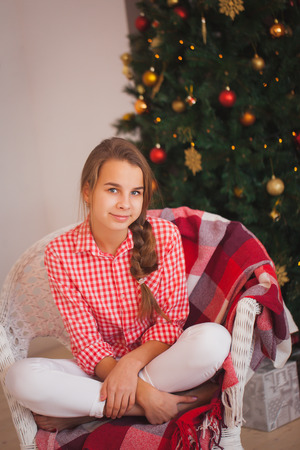 stock photo teen girl in a red plaid shirt in christmas decorations - Christmas Plaid Shirt