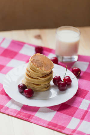 Tasty Pancake with fresh cherries on a white plate