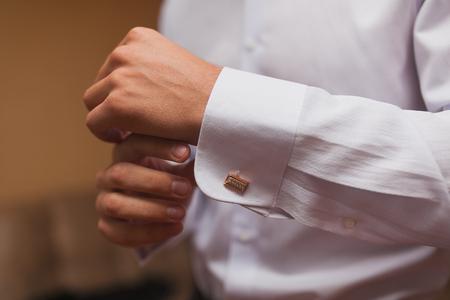 cuffs: Groom buttons cuffs on the shirt close-up. Wedding day.