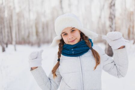 flaps: Cute teen girl smiling in winter park. Girl in a white hat with ear flaps and blue scarf laughs