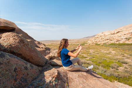 A cute girl in a blue T-shirt is sitting on a rock and is making a photo on a smartphone. Steppe with rare vegetation under blue sky. Landscape in Asia