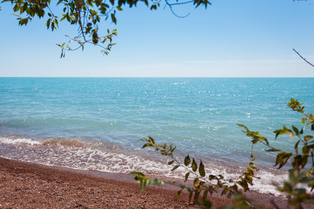 The shore line goes into the horizon. Blue water and sandy beach under the bright sun