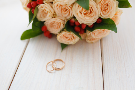 on a light wooden background lie engagement rings and a bouquet of the bride consisting of pink roses and berries. Selective focus
