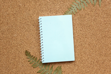 The notebook on a brown cork background with a dried fern. Place for text, mock-up for your design