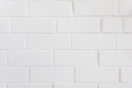 Neat white painted brick wall with a distinct texture. Perfect background for design. Place for text.