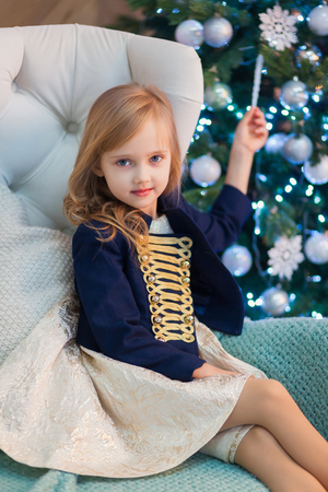 Close-up portrait of a little beautiful girl in a blue jacket against the background of the Christmas tree