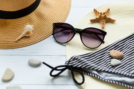 Sunglasses, hat and swimsuit on a white background. Vacation on the beach. Flatlay, top wiew