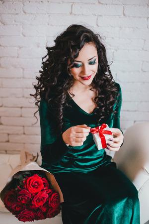 mujer con rosas: Mujer con lápiz labial rojo en el vestido de terciopelo verde y zapatos rojos con rosas rojas y collage de regalo. día de San Valentín