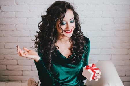 velvet dress: Woman with red lipstick in green velvet dress and red shoes and gift. Valentines Day