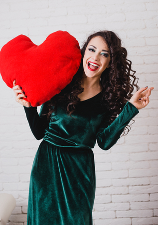 velvet dress: Beautiful happy woman with big red heart in hands. Valentines day theme Stock Photo