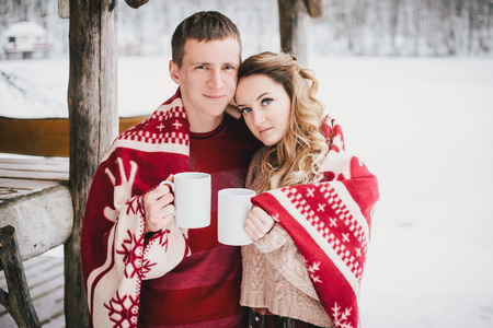 Happy couple with warm red blanket drinking hot tea in a snowy forest 版權商用圖片