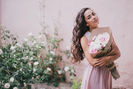 Young beautiful woman in a pink dress posing with a bouquet of peonies in a rose garden