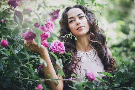 pink posing: Girl with long curly hair in pink dress posing in the garden Stock Photo