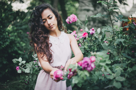beautiful rose: Girl with long curly hair in pink dress posing in the garden Stock Photo