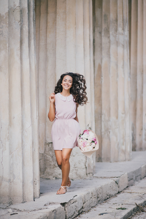 pretty dress: Beautiful girl in a pink dress with a bouquet of peonies posing near old columns. Spring mood Stock Photo