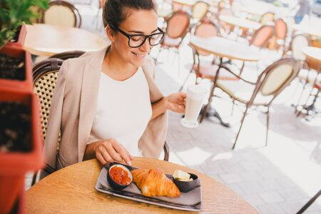 Young beautiful business woman wearing glasses having french breakfast in Paris street cafe Banque d'images