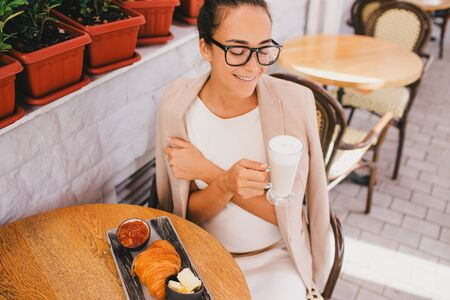 Young beautiful business woman wearing glasses having french breakfast in Paris street cafe 免版税图像
