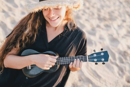 Beautiful young woman with long curly healthy hair wearing trendy straw hat playing ukulele at the beach. Standard-Bild