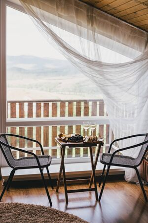 Table with wine, cheese, bread, grapes and pears standing on a cozy balcony in a wooden country house.