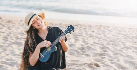 Beautiful young woman with long curly healthy hair wearing trendy straw hat playing ukulele at the beach. Banco de Imagens