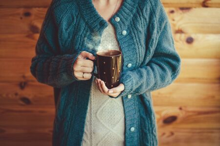 Woman in warm woolen knitted sweater witn cup of hot tea standing on cozy wooden balcony of country house.