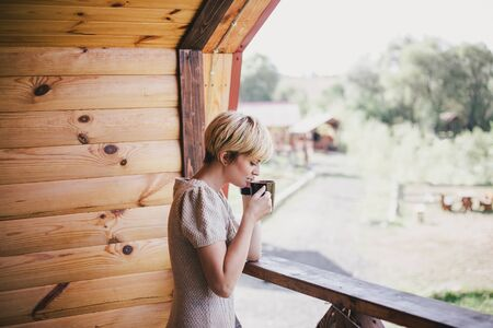 Young woman standing on the cozy wooden balcony with a cup of hot tea.