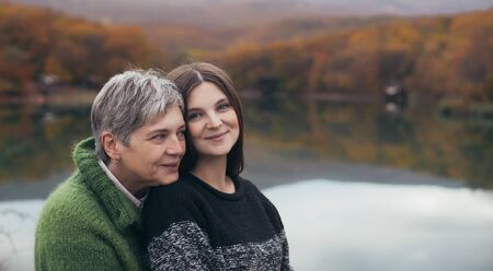 Senior mother and adult daughter hugging near lake with beautifu autumn forest on the background