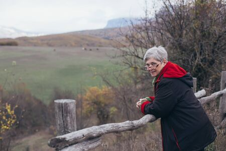 Senior woman with grey hair posing near wooden fence on the autumn background