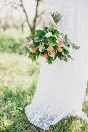 Bride holding wedding bouquet standing on the green grass in a garden.