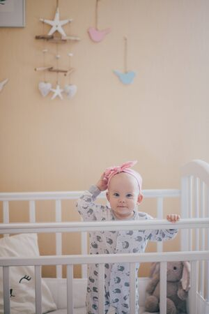 Adorable baby girl wearing cute pajamas standing in her white bed in a nursary room with beige walls. Stock fotó