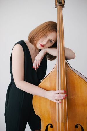 Beautiful young woman musician playing on a vintage double bass on a black background in a studio. Standard-Bild