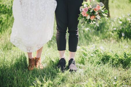 Bride and groom in wedding clothes feet close up. Rustic wedding concept.