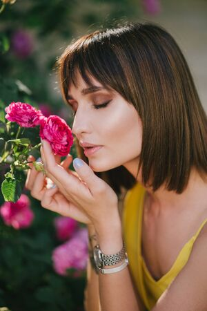 Young beautiful woman portrait close up with perfect skin posing with pink roses flowers in a garden. 写真素材