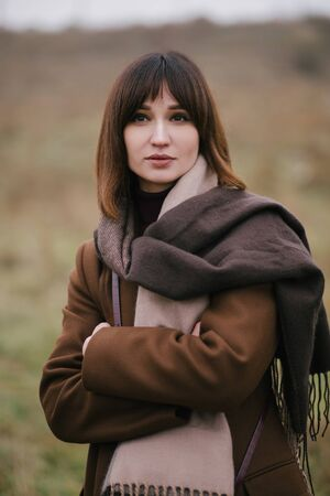 Young beautiful woman in brown stylish cashmere posing on the autumn landscapes background. Archivio Fotografico