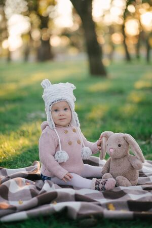 Little cute stylish baby in a knitted sweater and funny hat sitting on a grass with a bunny rabbit toy. 스톡 콘텐츠