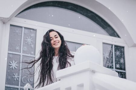 Young beautiful happy woman with long curly hair wearing white warm sweater standing under snowfall with lantern in hands with festive lights on the background. Christmas holiday concept. Stok Fotoğraf