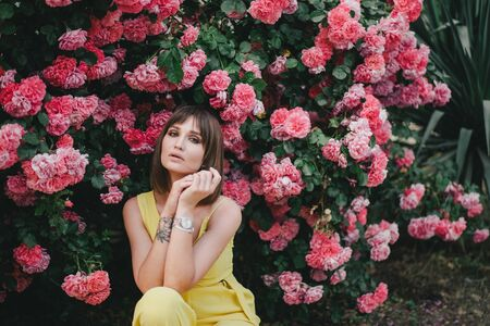 Young beautiful stylish woman in yellow jumpsuit with tattoo on her hand posing near roses flowers in a garden. 写真素材