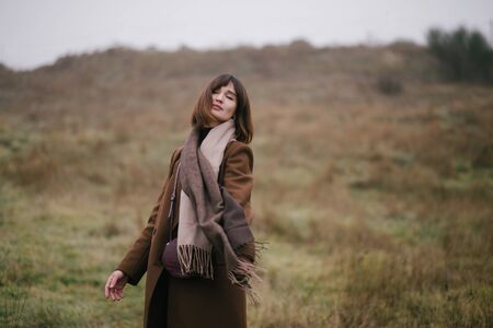 Young beautiful woman in brown stylish cashmere posing on the autumn landscapes background. Banque d'images