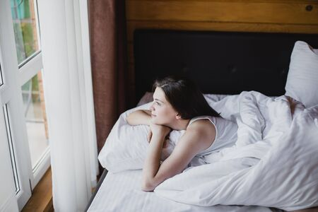 Beautiful young woman having good morning in bed with clean white linens in a cozy wooden house. She is looking at window and having dreamy mood.