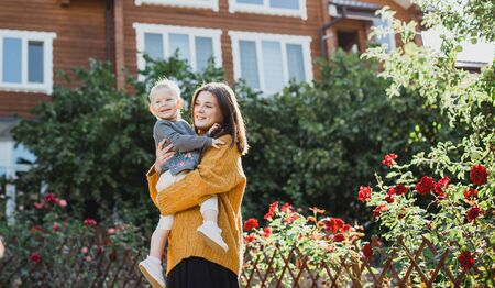 Young happy mother and her baby posing near their new cozy wooden house.