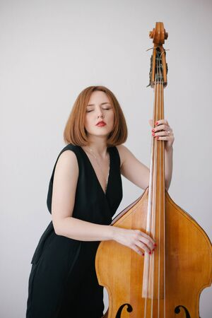 Beautiful young woman musician playing on a vintage double bass on a black background in a studio. Reklamní fotografie