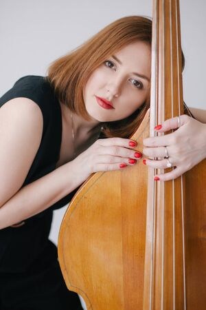 Beautiful young woman musician playing on a vintage double bass on a black background in a studio. 写真素材