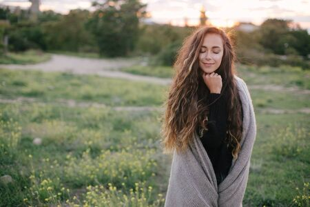 Young beautiful woman with a bright shining glittering make up standing on a green meadow with yellow flowers at sunset.