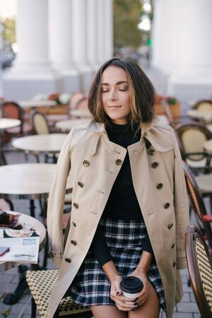 Young beautiful woman in trendy trench coat  drinking coffee in a street cafe.