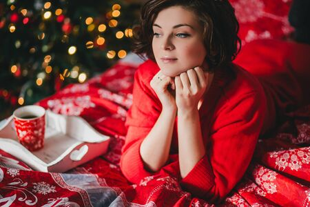 Young woman in a red knitted dress lying on the bed in bedroom with Christmas tree on the background
