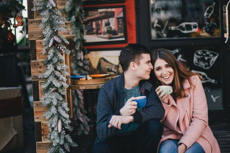 Happy couple in warm clothes drinking coffee on a Christmas market. Holiday mood Stockfoto