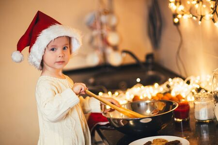 Cute baby girl in Santa Claus hat making Christmad cookies on decorated kitchen