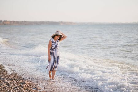 Happy plus size woman relaxing near ocean at the beach on sunny day. 스톡 콘텐츠