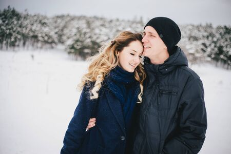Young happy couple spending holiday weekend in a winter snowy countryside Banco de Imagens