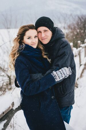 Young happy couple spending holiday weekend in a winter snowy countryside Banco de Imagens - 138373536